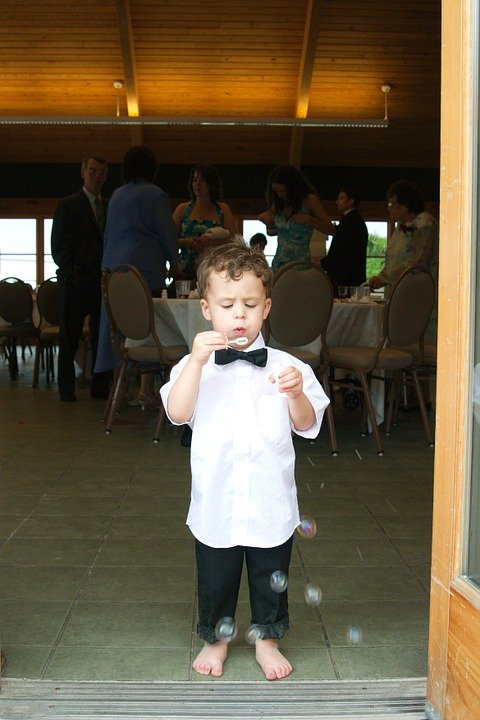 Ring bearer in tux blowing bubbles